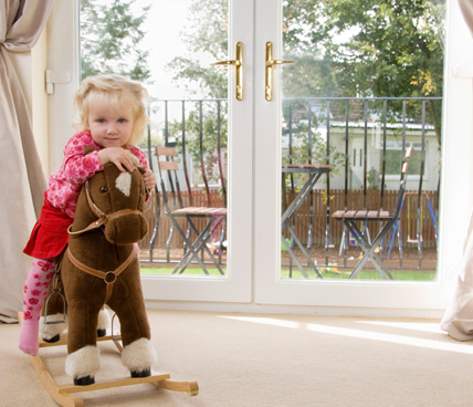 Toddler on rocking horse in front of French Door